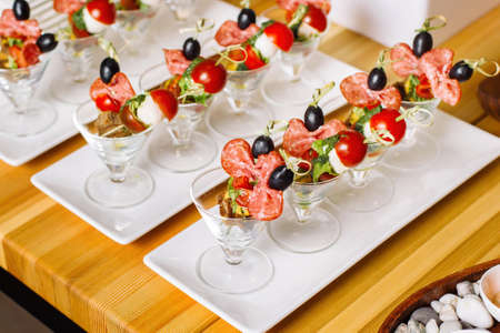 Canapes on toothpicks, appetizer, pinchos, spanish food. Quail eggs and cherry tomatoes.