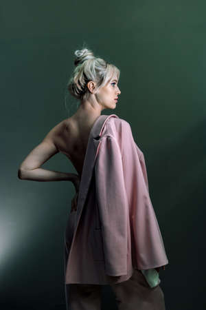 Sexy young blonde looking standing topless with a jacket in his hand. Full-length photo Reklamní fotografie