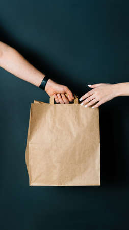 Disposable bag of kraft paper. Food delivery, hand-to-hand package transfer. Reklamní fotografie
