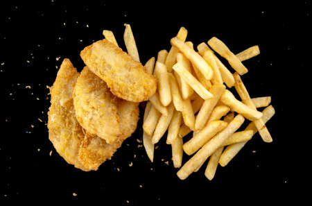 Image of French fries and deep-fried fish pieces. Two piles on a black background, top view. Macro photography.