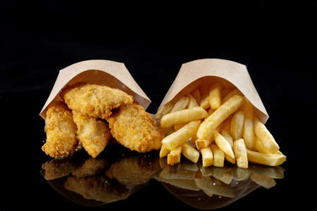 Image of French fries and deep-fried fish pieces. Fish and chips, in nice paper bags. Reklamní fotografie