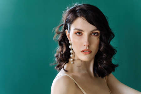 Elegant lady portrait.Pearls jewelry set posing isolated on studio green background.