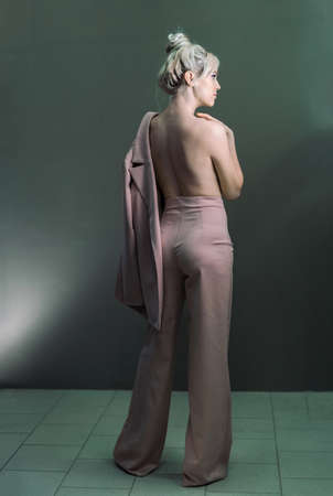 Sexy young blonde looking standing topless with a jacket. Keeps his hands on his chest. Photo from the back. Reklamní fotografie