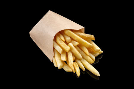 Potatoes fries in a little paper bag on a black mirrored background. Reklamní fotografie