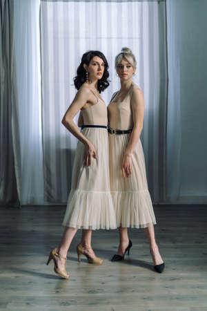 Studio portrait blondes and brunettes, looking at camera. Dressed in light designer dresses. One girl hugs another. Reklamní fotografie