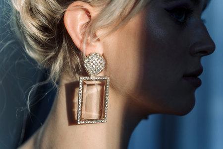 Close up studio portrait of a pretty blonde woman. Designer jewelry, shine on the neck.
