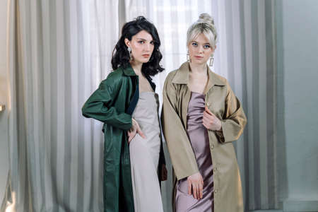 Young girls stands in the studio on the background of curtains. Stylish fashionable designer clothes. Banco de Imagens