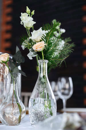 Beautifully served wedding table decorated with designer vases with bouquets.