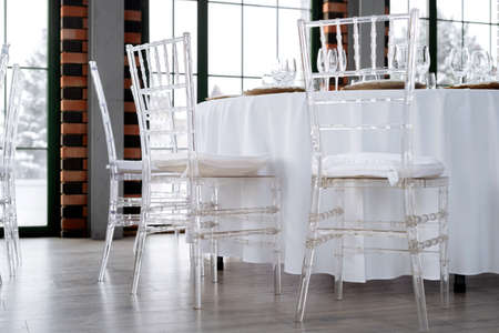 Transparent plastic chairs for wedding guests. Modern loft space, large windows.