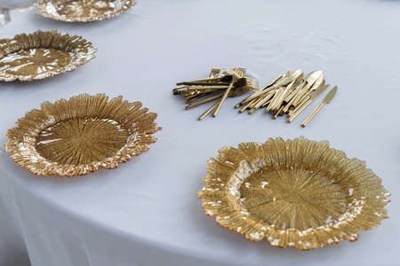 Beautiful served table, golden glass dishes, 45 view. Wedding event, luxury catering.
