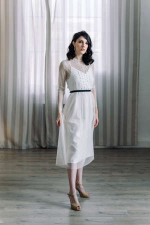 Cute young girl stands in the studio on the background of curtains. Looks at the camera and holds a dress with her hands, sad look.