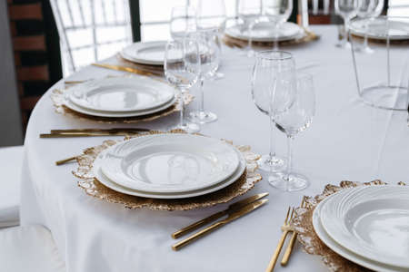 Beautiful served table, golden coasters, golden cutlery. Wedding event, luxury catering. Banco de Imagens