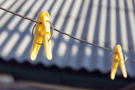 On the metal wire hang an old yellow plastic clothes pin.