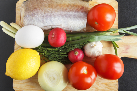 Foodstuffs for healthy balanced dish from various vegetables, egg and fish on closeup. Fresh organic tomatoes, rich in vitamins radish and garlic. Top view.