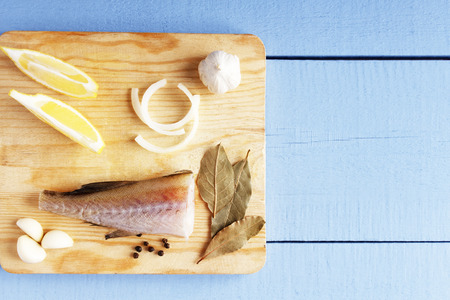 Top view on wooden table with ingredients for cooking. Vegetables and fish on cutting board. Healthy food concept. Top view with copy space.