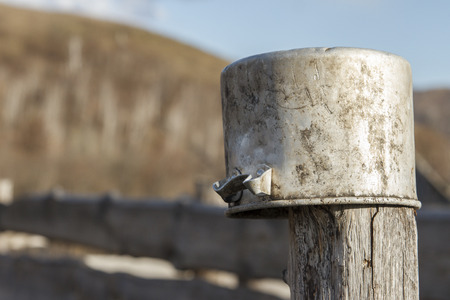 Old aluminum saucepan hanging on a wooden stanchion outdoors. Blurred copy space. Stock Photo
