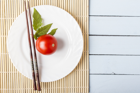 Fresh ripe tomatoes and food sticks on wooden table. White plate on bamboo mat. Top view with copy space.