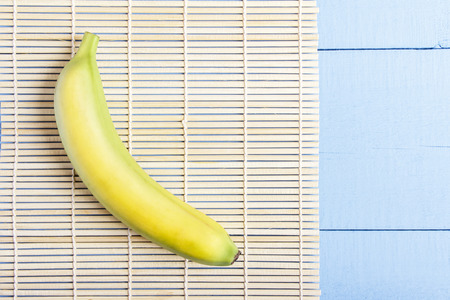 One ripe banana on bamboo mat. Top view on wooden table. Copy space. Stock Photo
