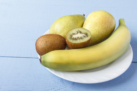 Pears, banana and kiwi fruit on white plate. Healthy breakfast or dinner with natural ripe fruits on wooden table. Side view. Copy space. Reklamní fotografie