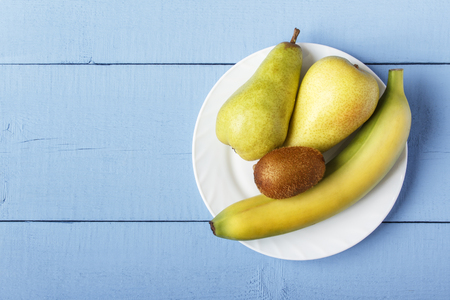 Top view on wooden ristic table with pile ripe fruit on white plate. Pears, banana and kiwi fruit for healthy breakfast or dinner. Copy space.