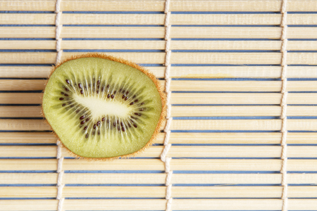 Natural organic kiwi fruits on bamboo mat for healthy breakfast and dinner. Copy space. Chinese and japanese kitchen concept. Top view. Stock Photo