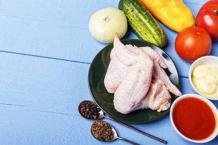 Rustic wooden table with raw ingredients for preparation of natural dish. Chicken wings, mayonnaise, tomato sauce, cucumber, onion and fragrant spices for healthy diet. Top view with copy space.