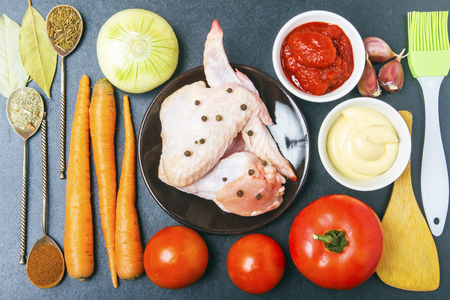 Fresh ingredients for healthy diet with chicken meat. Culinary brush and shovel, spices on silver spoons and tomato paste with mayonnaise on wooden table. Top view. Banco de Imagens - 106607966