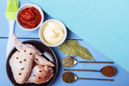 Chicken wings with black pepper, mayonnaise and tomato paste for rustic kitchen. Spoons with spices and bay leaves with culinary brush on wooden table. Copy space. Top view. Banco de Imagens