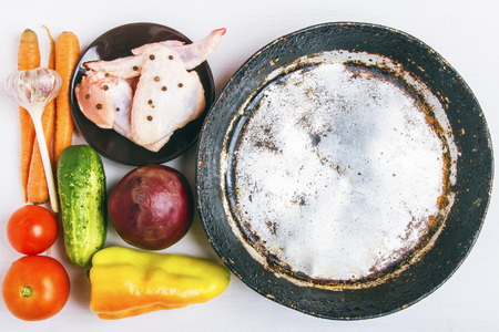 Fresh organic vegetables with chicken meat to prepare a rustic healthy dish. Empty aluminum frying pan for copy space. Healthy food concept. Top view. Banco de Imagens - 106607974