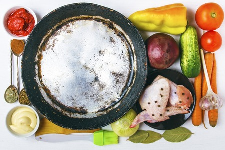 Fresh organic vegetables with chicken meat to prepare a rustic healthy dish. Empty aluminum frying pan for copy space. Healthy food concept. Top view. Banco de Imagens