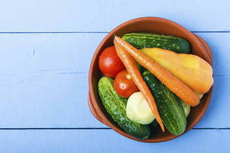 Fresh whole vegetables in ceramic bowl on wooden table. Healthy food concept. Top view from above. Copy space.