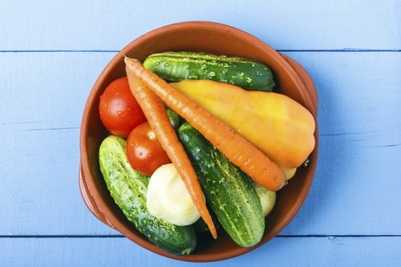 Organic cucumbers, tomatoes, carrots, bell pepper and onoin for vegetarian food. Healthy lifestyle concept. Top view from above. Copy space.