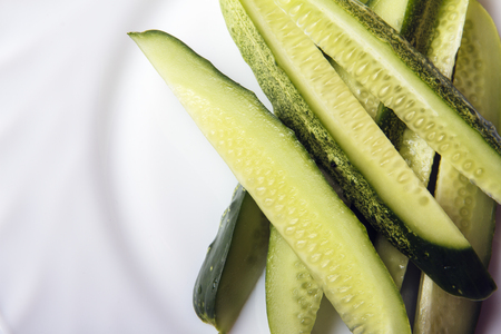 Sliced organic cucumbers on white plate with space for text or copy space. Top view. Banco de Imagens - 106608033