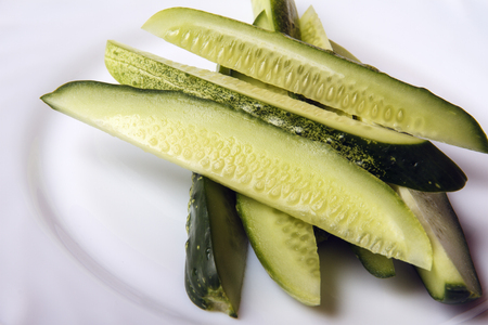 Sliced organic cucumbers on white plate. Dietary food for healthy lifestyle Top view. Banco de Imagens - 106608034