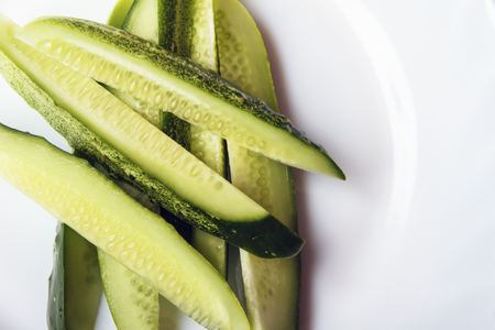 Sliced organic gherkins on white plate with space for text or copy space. Dietary food for healthy lifestyle. Top view. Banco de Imagens