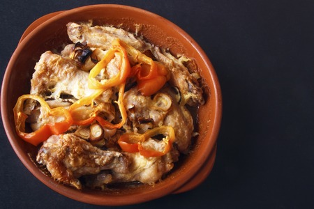 Chicken wings baked in oven with sweet pepper and onions on black background. Top view. Copy space. Banco de Imagens - 106743817