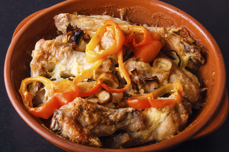 Hot appetizer of chicken meat in ceramic bowl. Dish is baked in oven.