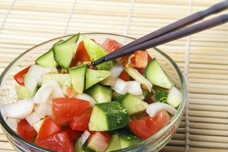 Healthy breakfast or dinner from natural organic cucumbers, tomatoes and onion on bamboo mat. Chinese or japanese kitchen concept. Copy space. Banco de Imagens