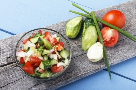 Fresh salad from organic vegetables on wooden board. Vegetarian and vegan food. Copy space.