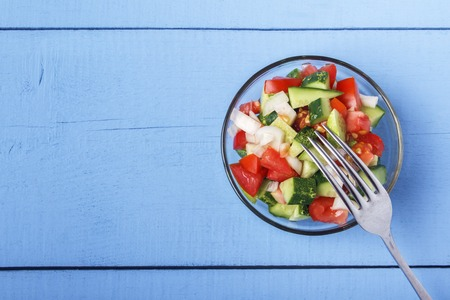 Chopped vegetables - cucumbers, tomatoes and onions in glass bowl on wooden table. View from above. Copy space