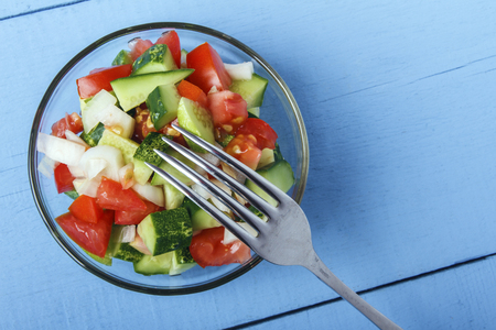 Chopped vegetables - cucumbers, tomatoes and onions in glass bowl on wooden table in closeup. View from above. Copy space.
