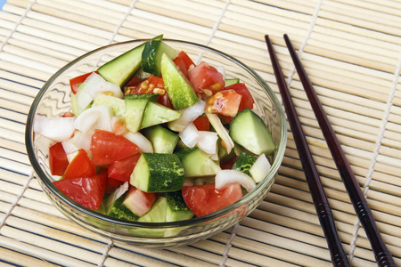 Fresh salad from organic natural vegetables and chopstick on bamboo mat. Chinese or japanese kitchen concept. Copy space. Banco de Imagens - 106743858