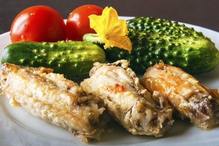 Baked poultry chicken wings, fresh natural tomatoes and green organic cucumbers on a white plate on a black background in closeup. Healthy healthy food for dinner or lunch. Banco de Imagens - 106743860