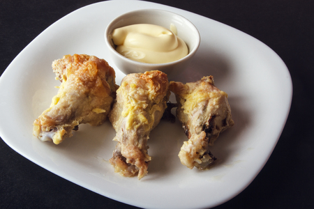 Baked poultry meat and mayonnaise on white plate. Delicious and dietary lunch or dinner on dark background. Banco de Imagens