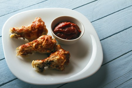 Crispy chicken wings. Freshly cooked dish on a white plate on a wooden table. View from above with copy space.