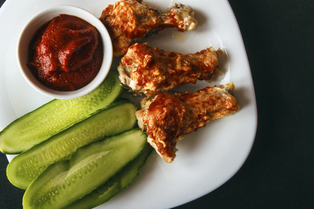 Baked poultry chicken wings, tomato paste and sliced cucumbers on a white plate on a black background. Top view from above. Copy space for text. Banco de Imagens