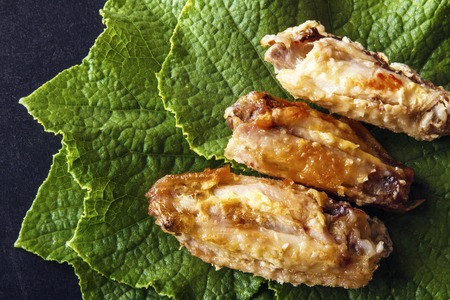 Baked crispy chicken wings on green cucumber leaves on a black background. Top view from above. Copy space for text. Banco de Imagens - 106743868
