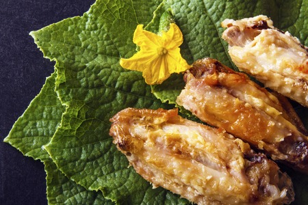 Baked crispy poultry chicken wings on green cucumber leaves on a black background. Top view from above. Copy space for text.