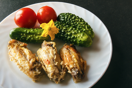 Baked chicken wings, fresh tomatoes and green cucumbers on a white plate on a black background. Dietary healthy food for dinner. Copy space. Banco de Imagens - 106743870