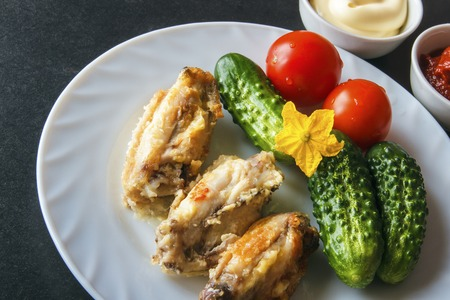 Baked chicken wings in tomato paste and mayonnaise on a white plate with fresh organic vegetables on a black background. Copy space. Banco de Imagens - 106848707
